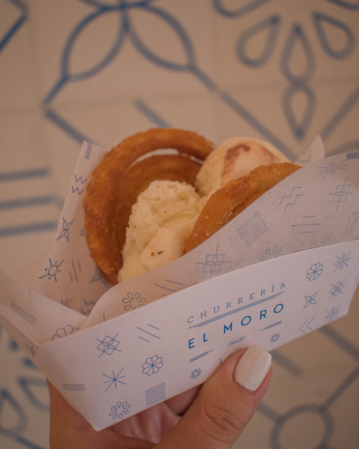 A churro ice cream sandwich placed against the bright blue and white tiles of El Moro Churrería in Mexico City.
