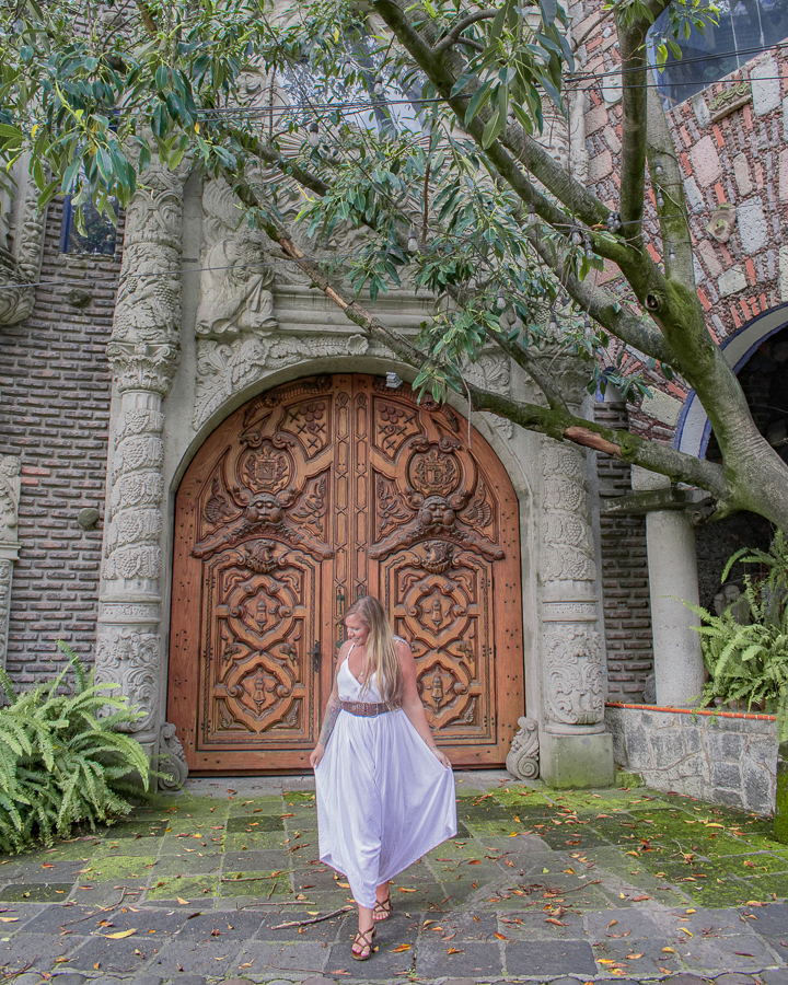 Jacklyn Shields poses in front of an intricately carved door belonging to a residence in the Chimalistac area of Mexico City, Mexico.