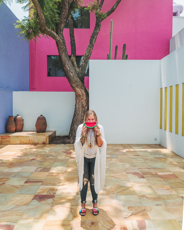 Jacklyn Shields poses with a slice of a watermelon in the colorful home, Casa Gilardi, designed by Luis Barragán.