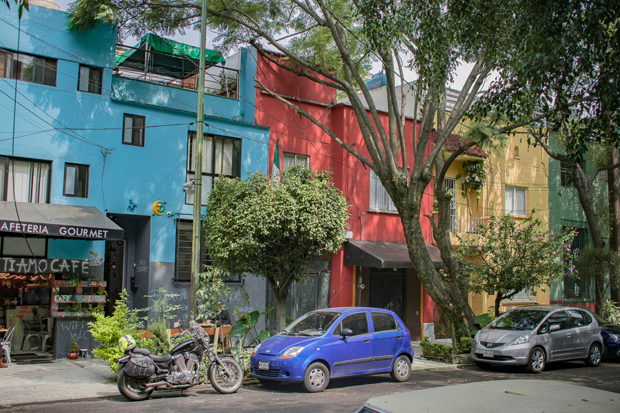 A cute café in a bright blue hue and other brightly colored the facades in the streets of Mexico City.
